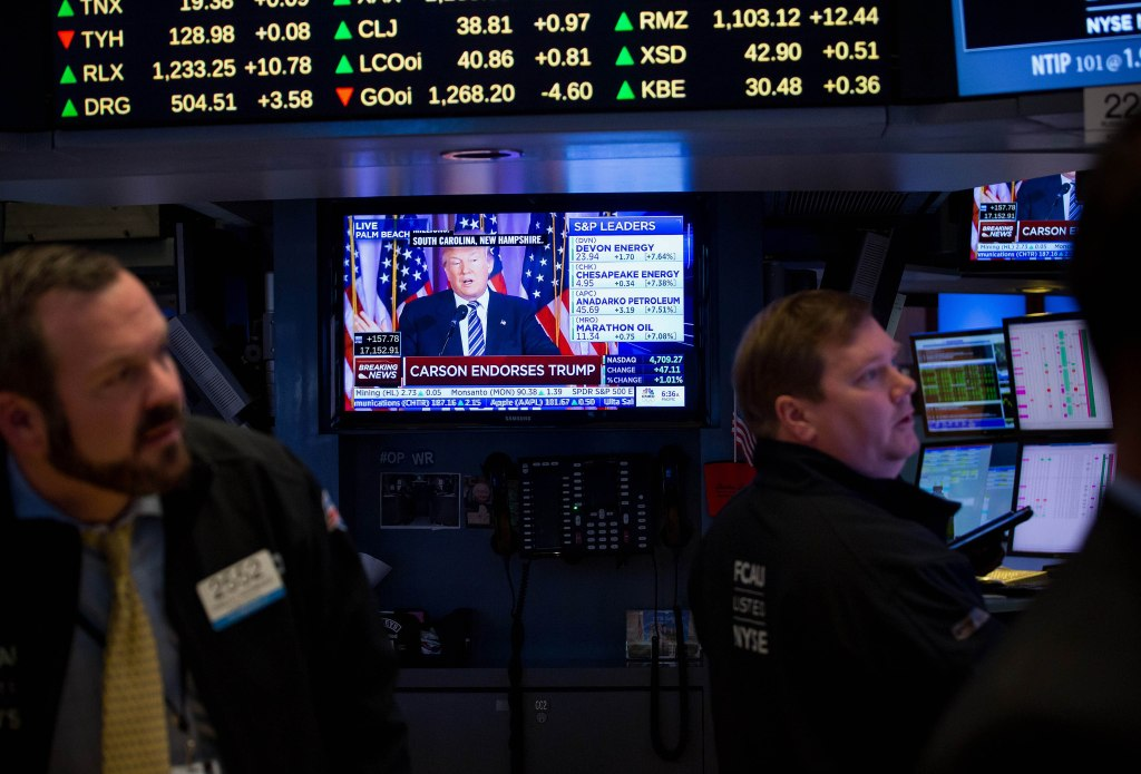 Donald Trump, president and chief executive of Trump Organization Inc. and 2016 Republican presidential candidate, is seen speaking on a monitor as traders work on the floor of the New York Stock Exchange (NYSE) in New York, U.S., on Friday, March 11, 2016. U.S. stocks rose to join a global rally, poised to erase a weekly decline as investors reassessed stimulus measures in Europe and warmed to the steps taken to boost growth. Photographer: Michael Nagle/Bloomberg via Getty Images